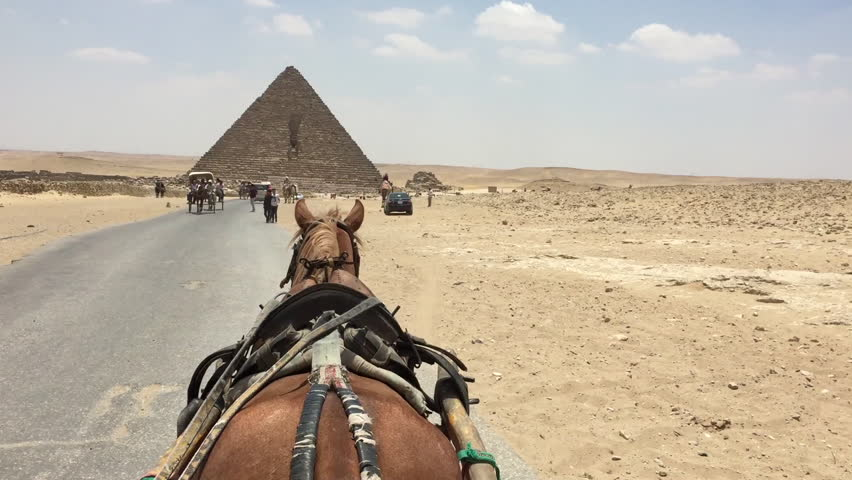 GIZA, CAIRO - EGYPT - MAY 2017: A horse and buggy pov unique point of view of the pyramids in Egypt. Tourism industry is battered and bruised due to Coptic church bombings and airline bombings.