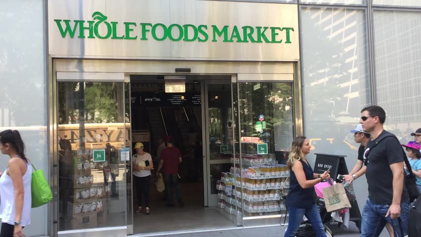 NEW YORK CITY - JULY 18, 2017: Whole Foods Market (WFM) exterior and logo. Whole Foods Market Inc. is American supermarket chain acquired by Amazon (AMZN), expanding presence as a physical retailer.