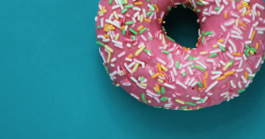 Delicious sweet donut rotating on a plate. Top view. Bright and colorful sprinkled donut close-up macro shot spinning on a blue background. Delicious sweet donut rotating on a plate. Top view | Shutterstock HD Video #29258188