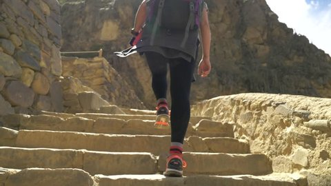 Woman Walking up Incan Steps.  Hiking up ancient rock steps in the ruins of Ollantaytambo Peru.  Slow Motion