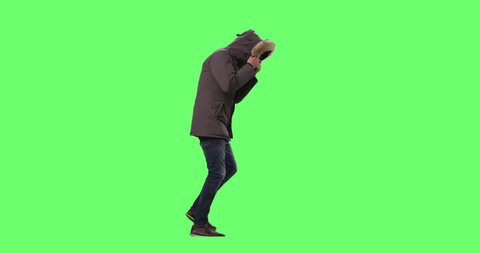Man in a Wearing Winter Jacket with Hood On Walks Against Cold Weather and Strong Wind. Shot on a Mock-up Green Screen Background. Shot on RED Cinema Camera in 4K (UHD).