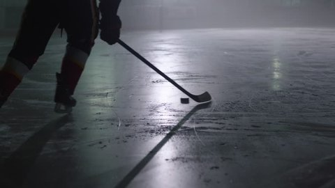 ice hockey stick handling puck player skating skates in an arena in slow motion