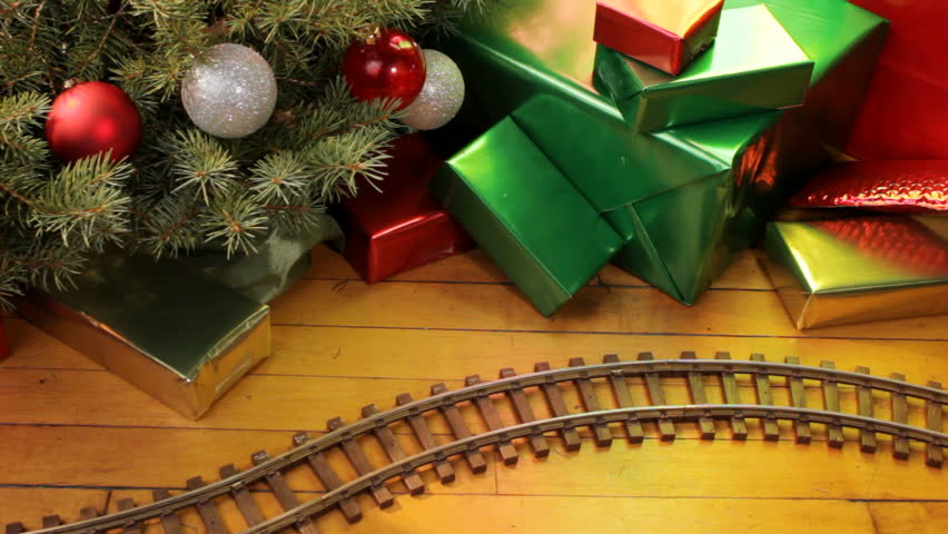 Toy electric train filled with decorations passes along wood floor on Christmas morning