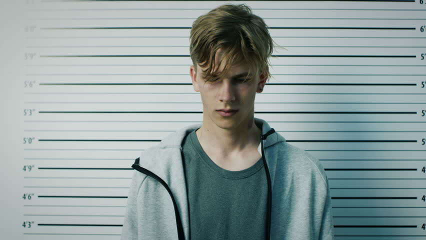 In a Police Station Arrested Teenage Delinquent Poses for Side, Front View Mugshot. He is Heavily Bruised. Height Chart in the Background. Shot on RED EPIC-W 8K Helium Cinema Camera.