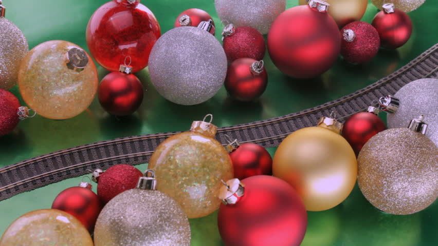 Toy electric train passes through colorful christmas tree decorations shot at