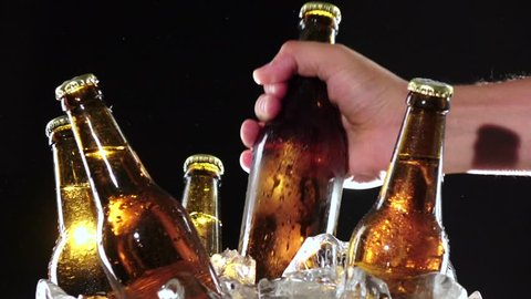 Hand takes a bottle of cold beer. Black background . Close up