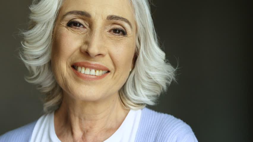 Portrait of happy old woman with eyeglasses smiling and looking at camera. Indoor shot. Close up.