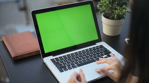 Closeup woman sitting table notebook female hands keyboarding laptop using texting pointing networking green screen chroma key chromakey keyboard white device working message student businesswoman