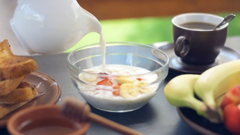 Cinemagraph -Fresh granola, muesli with berries and pouring milk in a  bowl. Motion Photo. Healthy breakfast.