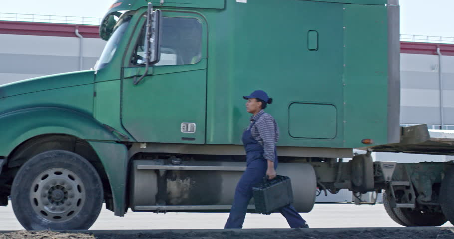 Slow motion side view of black female mechanic walking with tool case along truck