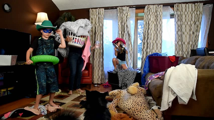 A housewife is stressed and tired trying to clean the house while wild children are running around making a mess for a discipline or parenting concept.