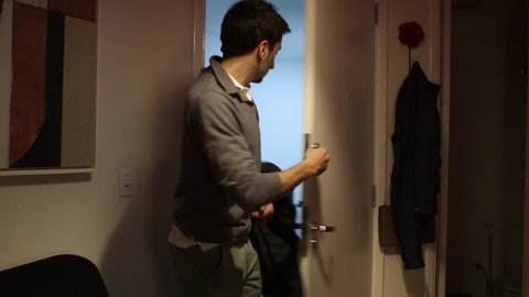 Person enters home through front door. Bachelor enters home,  turns on the lights, and puts overcoat on holder