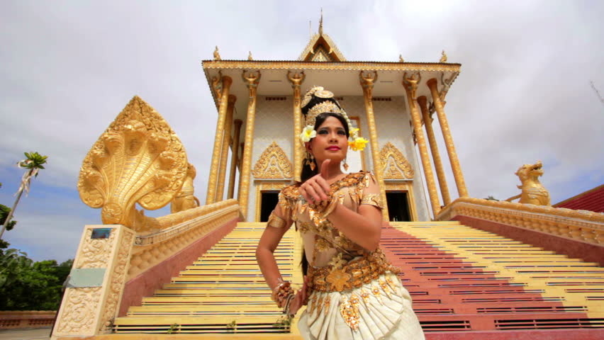 Apsara Dancer dancing near a temple in the afternoon