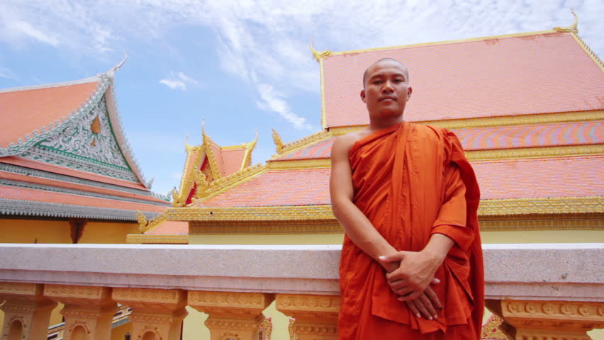 A kind Buddhist monk with orange robe pray in temple