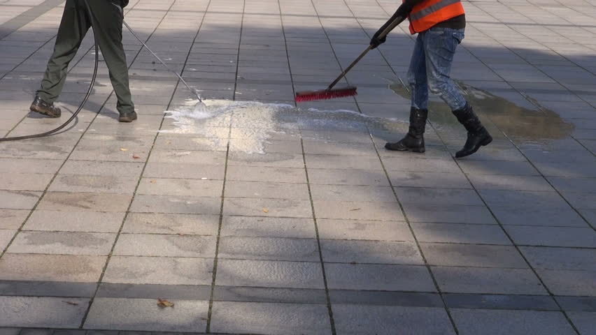 workers cleaning city square granite pavement