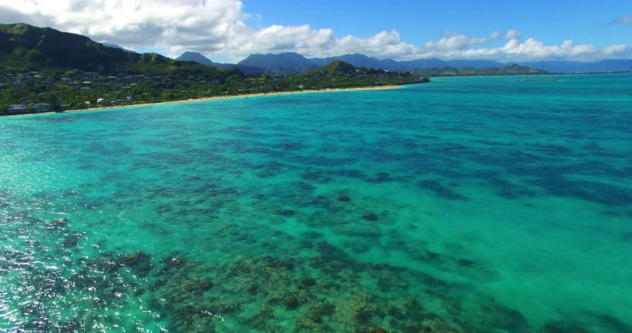Aerial Footage of Shallow Reef with Unidentifiable Kayaker Paddling in Turquoise Blue Water