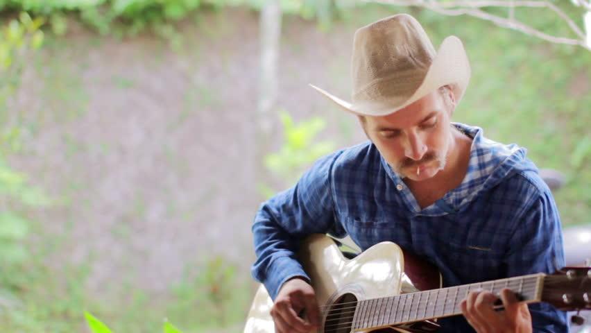cool cowboy Caucasian man playing guitar