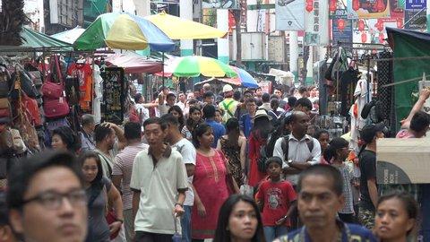 KUALA LUMPUR, MALAYSIA - MAY 2017: Locals and tourists walk through popular Jalan Petaling shopping street in Kuala Lumpur's Chinatown, travel Malaysia