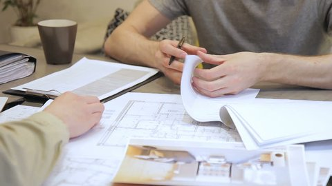 Chief architect signs documents and gives it to colleague in office indoors