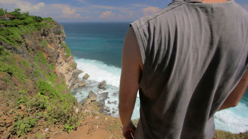 suicidal young man at the edge of cliff overlooking ocean