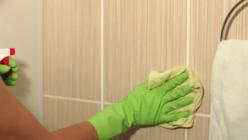 Close-up woman washer is cleaning tiled surface in bathroom. The girl is holding a cleaning spray and a sponge in his hands. 4K