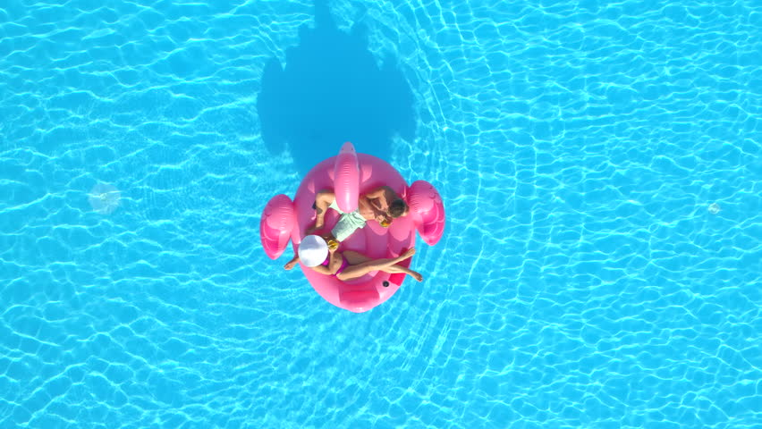 AERIAL TOP DOWN Young couple toasting and drinking cocktails while lying on fun inflatable flamingo floatie. Sexy couple in swimsuit sipping drinks and relaxing on pink flamingo floating on pool water