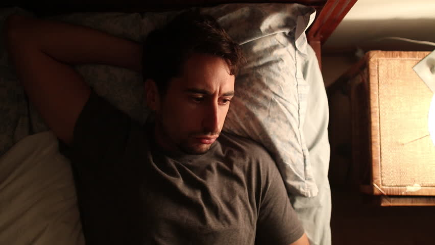 Man wakes up in the middle of the night - turns on nightstand lamp worried about insomnia and gets out of bed. Person with thoughtful look on face is concerned about something