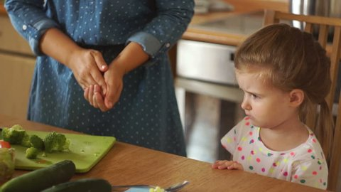 Little girl in the kitchen with her mother. Mom gives the daughter broccoli. The girl resolutely repels the vegetables with her hand. The baby is very angry and does not want to eat.