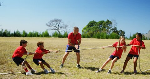 Trainer assisting kids in tug of war during obstacle course training in the boot camp