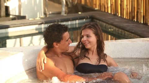 Attractive couple relaxing in spa Jacuzzi during honeymoon