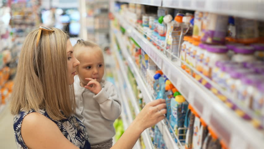 Mom with baby look for child's fruit puree and juices inside of market place, walking between shops shelves, carefully choose the kids products. Beautiful pretty wonder infant take packet at hands | Shutterstock HD Video #29461045