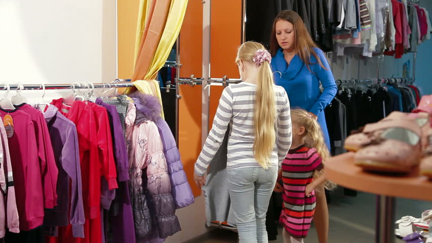 820480f8430 Mother with two daughters shopping for girls clothes in a clothing store,  child trying on dress