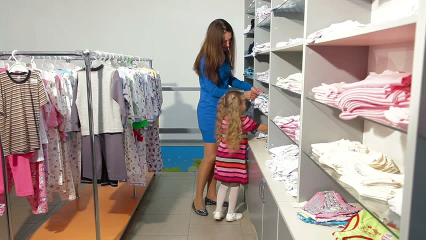 mother with two daughters shopping for girls clothes in a