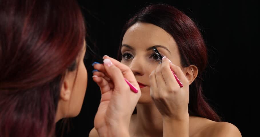 Beautiful Young Woman Applying Makeup on Eyebrows Using Paint Brush Beauty Salon #29465434