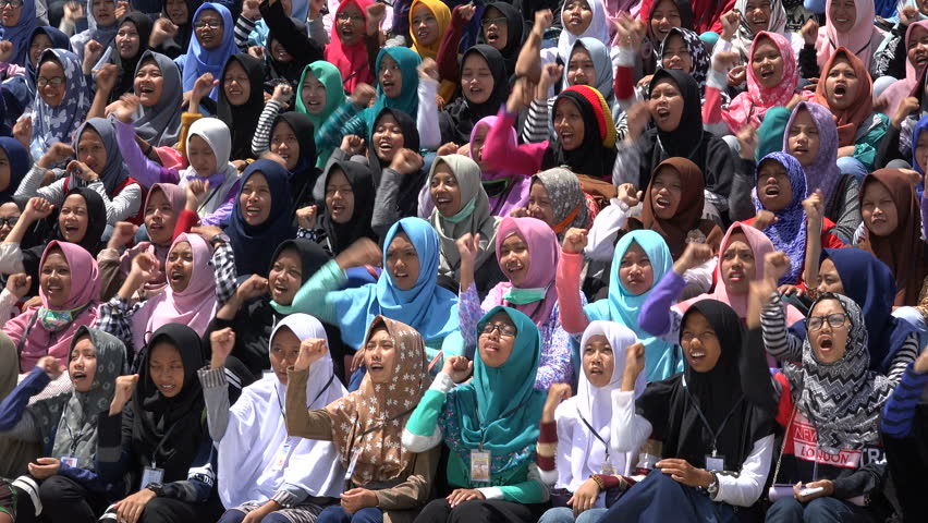JAKARTA, INDONESIA - APRIL 2017: Veiled Muslim school girls chant 'Allahu Akbar' while clenching fists, colorful headscarves, Islamic religion in Jakarta, Indonesia