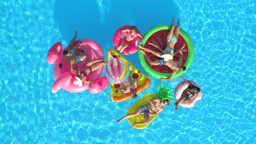 AERIAL TOP DOWN Cheerful girls and guys playing with ball on colourful floaties in pool. Smiling friends enjoying summer vacation on inflatable pineapple, pizza, flamingo, watermelon, doughnut floats