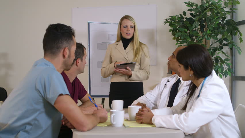 Lovely blond pharmaceutical saleswoman giving a presentation to a group of doctors sitting at a table.