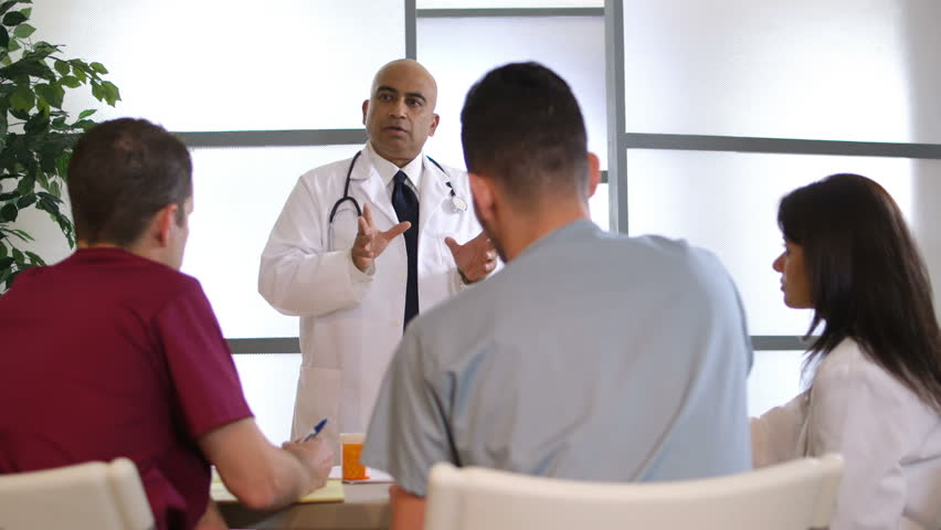 An Indian physician stands in front of a small group of fellow doctors giving a talk. Canon C300