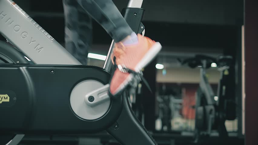 Young beautiful girl in gym, shaking her legs on cycling simulator, smiling at camera. The concept: to love sports, to attend a gym, proper nutrition, a slender body, to be healthy.