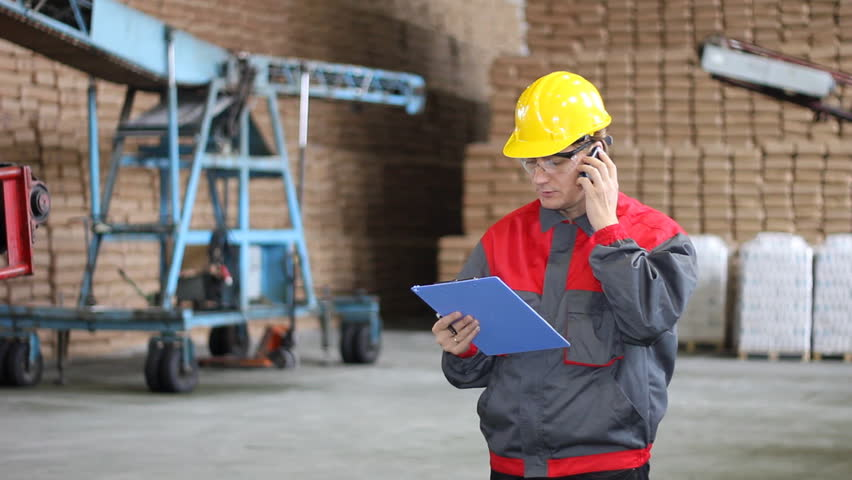 Man working in Warehouse, controlling and writing the results of the quality and number of bags in a sugar refinery, He's talking on cellphone