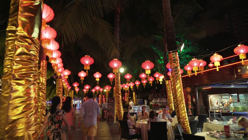 Sanya, China - April 06, 2017: Walking on a night tourist promenade with restaurants on Dadonghai beach stock footage video | Shutterstock HD Video #29537638