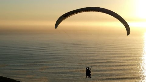 Paragliding into sunset seascape, with pilot adjusting wing controls, changing direction, sunset lit ocean waves, sun beam trail to horizon, two small distant boats, yellow orange light, horizon