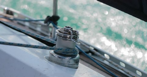 Sailing, man pulling ropes, winding sheets around winches. close-up.  real time