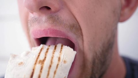 to bite into a delicious Shawarma , closeup. slow motion. 1920x1080. full hd