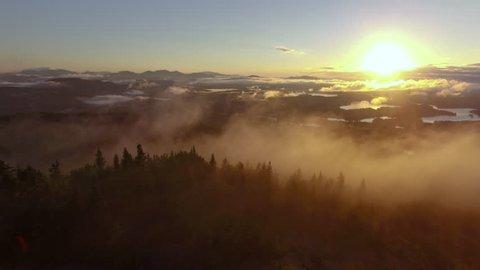 Aerial shot through golden misty mountains