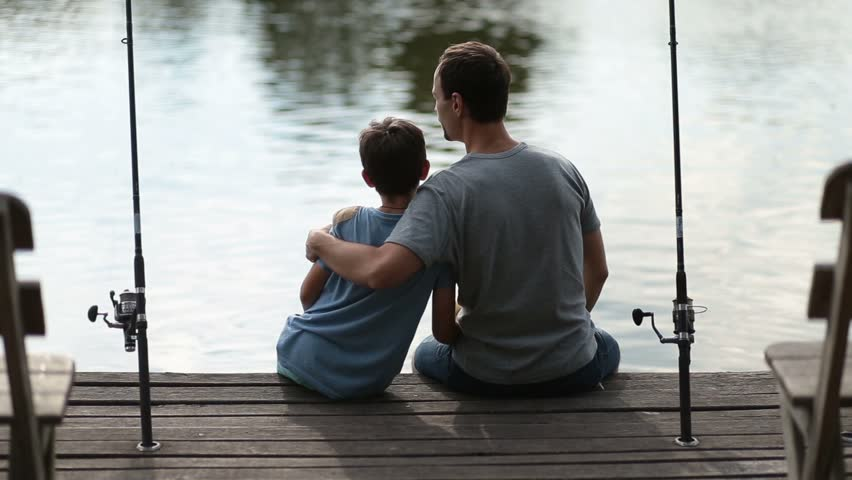 Affectionate father embracing son as they fish | Shutterstock HD Video #29591278