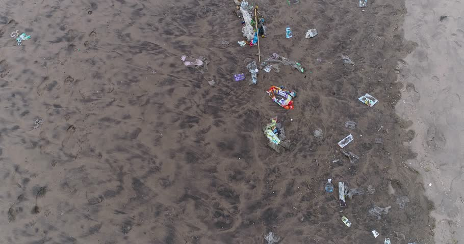 Drone footage of plastic waste washed ashore on the beach in Seminyak, Bali. The camera is facing down at the trash on the sand and is going along the beach.