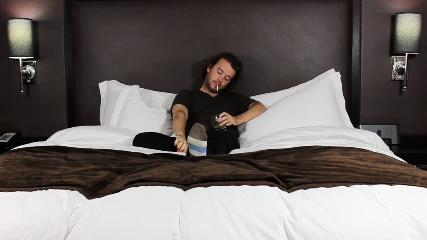 Hip young man lies in swanky hotel bed | Shutterstock HD Video #2960578