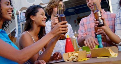 Group of friends toasting beer bottles in food truck