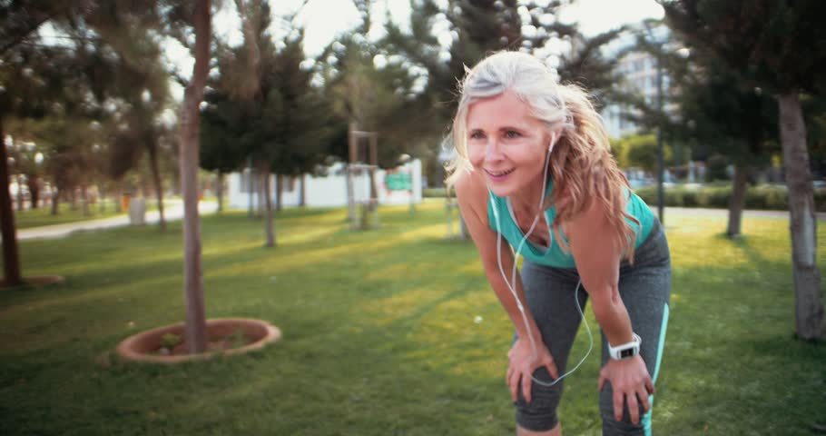 Fit senior woman with earphones and smartwatch resting after running in the park | Shutterstock HD Video #29619418